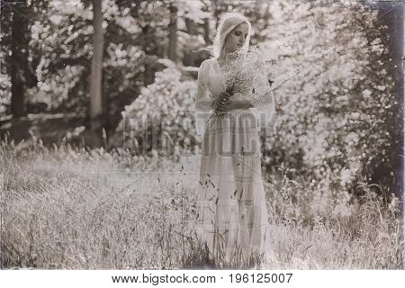 Vintage Black And White Photo Of Hippie Bride Holding White Flowers Standing In Forest
