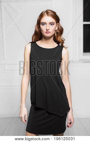 Portrait of nice woman wearing black dress posing in the studio
