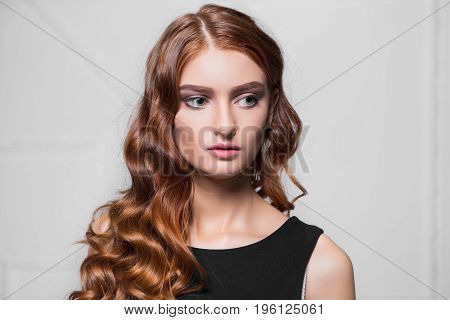 Portrait of thoughtful curly woman posing in the studio