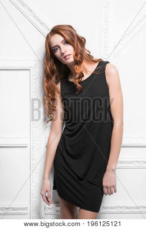 Portrait of lovely woman wearing black dress posing in the studio