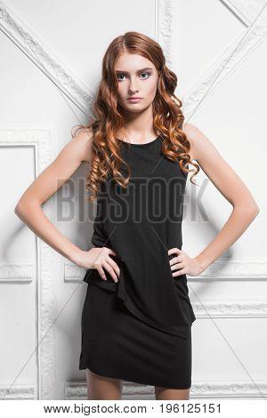 Portrait of cute woman wearing black dress posing in the studio