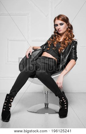 Attractive curly lady wearing black fashionable clothes sitting in a chair