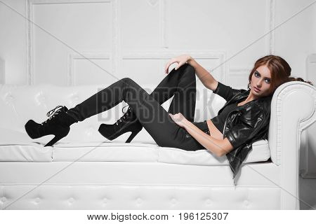 Leggy young model lying on the sofa in black fashionable clothes