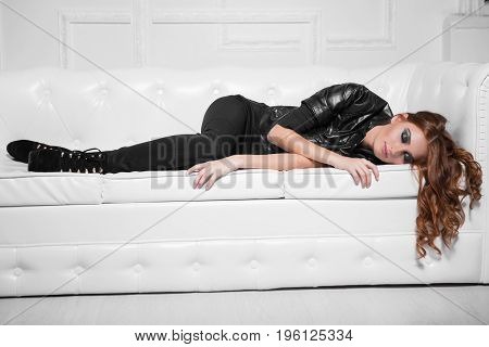 Pretty red-haired lady lying on the sofa with closed eyes