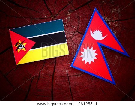 Mozambique Flag With Nepali Flag On A Tree Stump Isolated