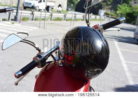 Helmet of a motorcyclist leaning over a motorcycle