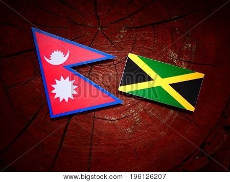 Nepali Flag With Jamaican Flag On A Tree Stump Isolated