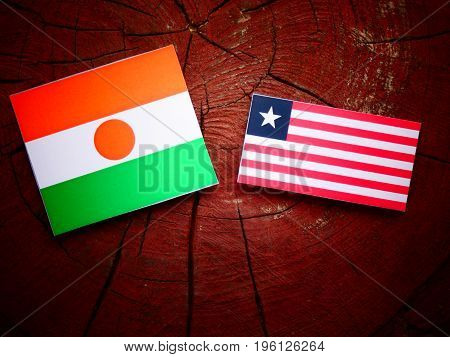 Niger Flag With Liberian Flag On A Tree Stump Isolated