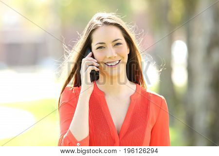 Front view portrait of a happy woman wearing an orange blouse calling on phone and looking at you in the street