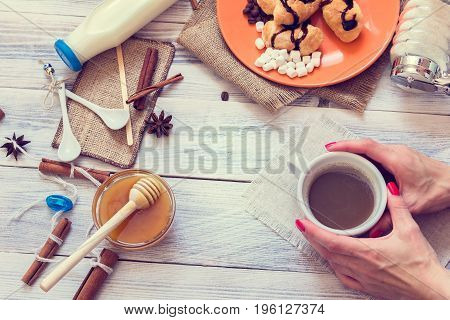 Female hands hold a cup of coffee in the background with croissants honey and milk