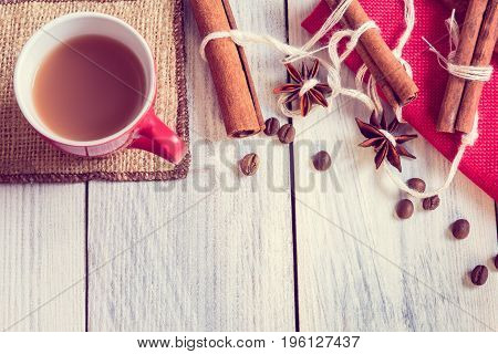 Red cup with espresso on burlap with anise and cinnamon on a wooden background