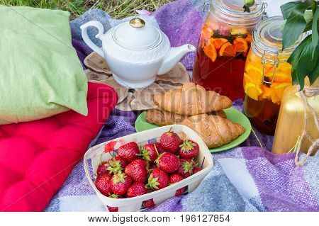 Picnic in the outdoor with tea croissants strawberry and different beverages