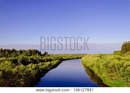 View of a small river on a summer evening