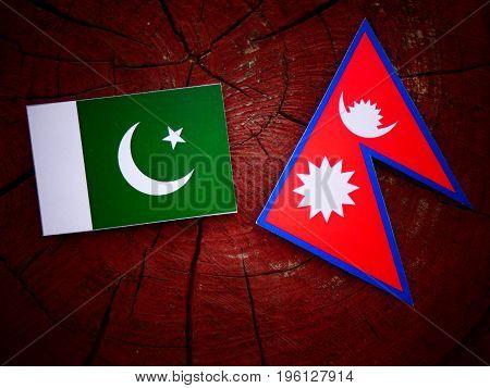 Pakistani Flag With Nepali Flag On A Tree Stump Isolated