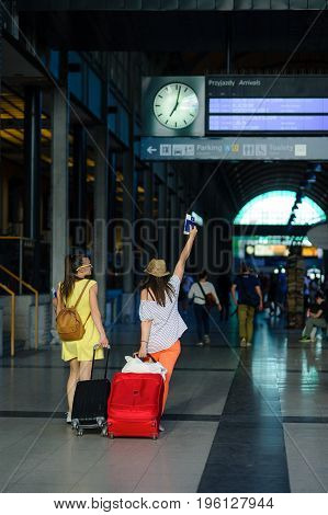 Young women hurry to their train. They roll their suitcases. The tourists are in a good mood. Summer vacation.