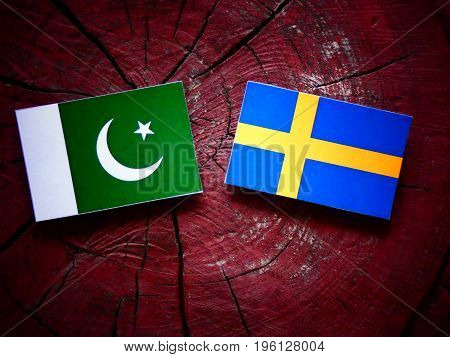 Pakistani Flag With Swedish Flag On A Tree Stump Isolated