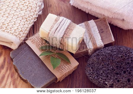 Three pieces of dry soap with a towel pumice and a bast on a wooden background