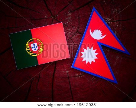 Portuguese Flag With Nepali Flag On A Tree Stump Isolated