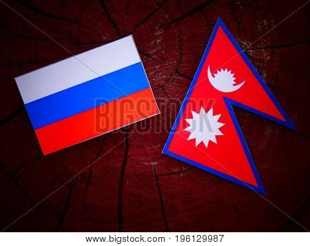 Russian Flag With Nepali Flag On A Tree Stump Isolated