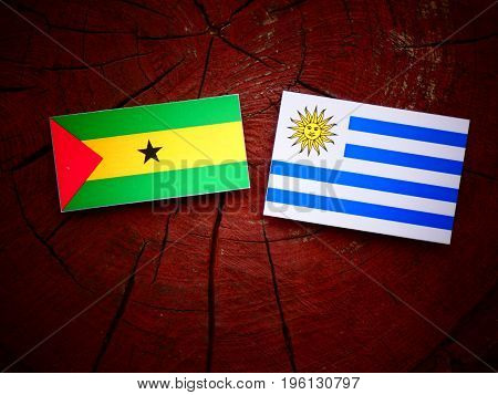 Sao Tome And Principe Flag With Uruguaian Flag On A Tree Stump Isolated
