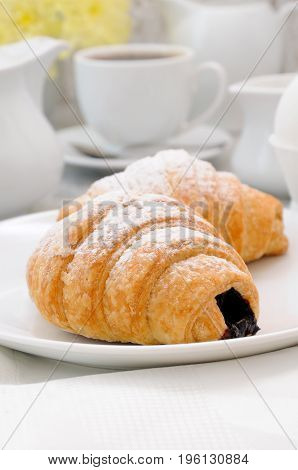 Croissants with chocolate filling cup and fresh morning coffee. Foreground close-up