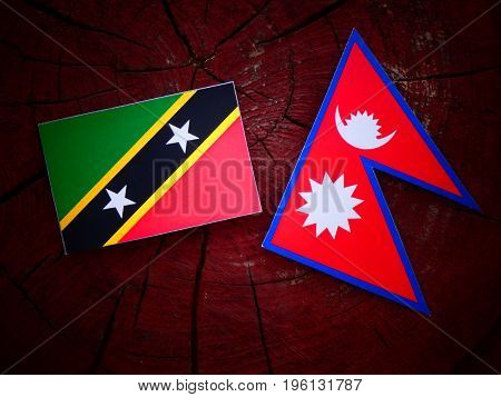 Saint Kitts And Nevis Flag With Nepali Flag On A Tree Stump Isolated