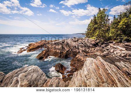 Scenic rocky shoreline in La Verna Preserve in Bristol, Maine, on a bright summer day