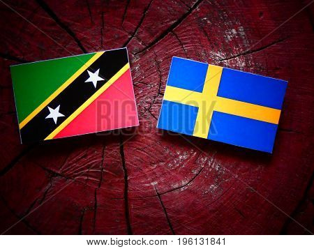 Saint Kitts And Nevis Flag With Swedish Flag On A Tree Stump Isolated