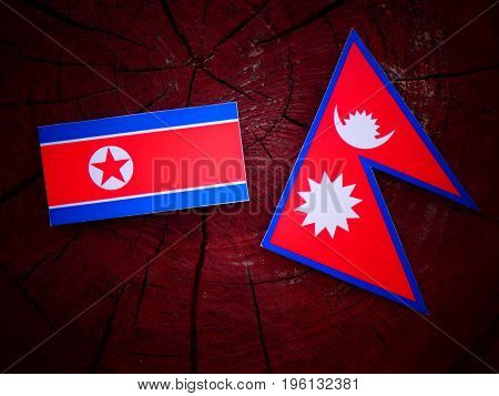 North Korean Flag With Nepali Flag On A Tree Stump Isolated
