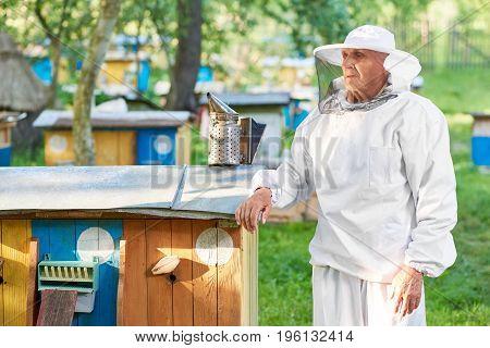 Senior beekeeper in a beekeeping suit posing near beehive at his apiary looking away thoughtfully copyspace.