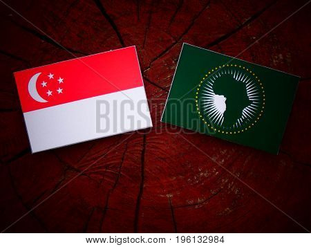 Singaporean Flag With African Union Flag On A Tree Stump Isolated