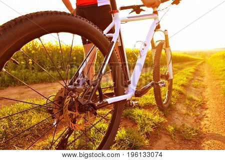 Cyclist with mountain bike on dirt road at sunset. Healthy lifestyle concept.