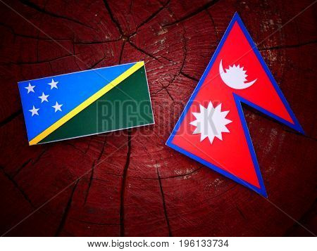 Solomon Islands Flag With Nepali Flag On A Tree Stump Isolated