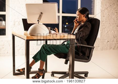 African american businesswoman sitting in her chair at the table and talking on the phone.