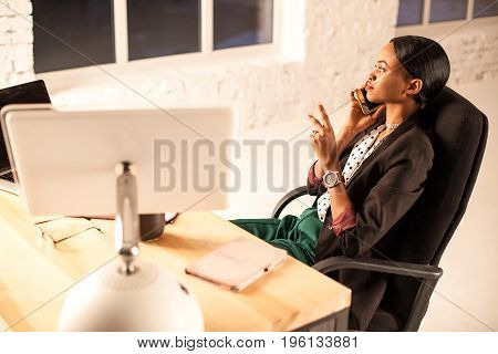 Pretty businesswoamn sitting in fronf of the computer in her office and talking onthe phone.