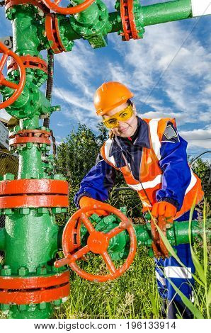 Woman worker in the oilfield repairing wellhead, wearing orange helmet and work clothes. Industrial site background. Oil and gas concept.