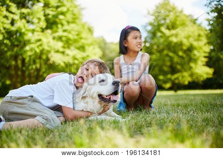 Child hugs Golden Retriever dog with affection and love
