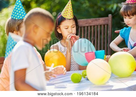 Children celebrate with colorful balloons and hats at birthday party in garden