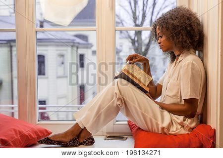 Slender african american girl sitting on the windowsill with the book in her hands.