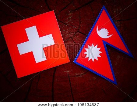Swiss Flag With Nepali Flag On A Tree Stump Isolated