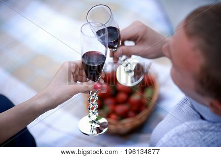 man and girl having picnic in forest. Blond woman in dark blue dress and man in light trousers and shirt. couple looking in each other and drink wine. happy family relationship concept