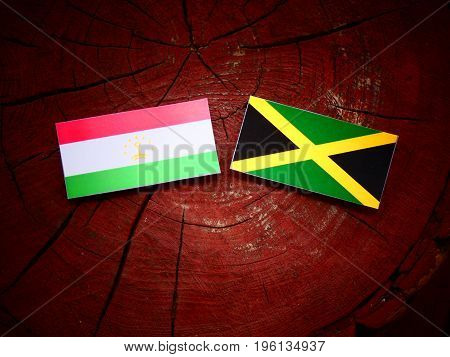 Tajikistan Flag With Jamaican Flag On A Tree Stump Isolated
