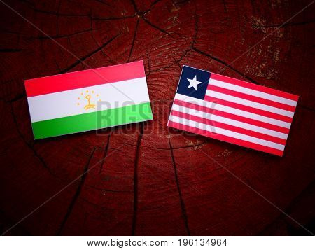 Tajikistan Flag With Liberian Flag On A Tree Stump Isolated