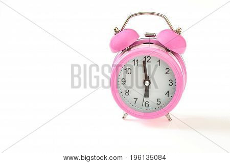 Vintage pink alarm clock with 6 o'clock on it. Isolated on white background