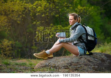 Young girl hiker enjoying the view and write down her thoughts to her diary