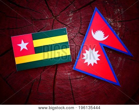 Togolese Flag With Nepali Flag On A Tree Stump Isolated