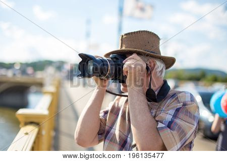Senior tourist man in hat photographing during trip on bridge
