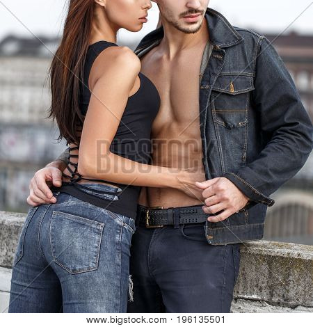 Young woman touching sexy boyfriends abs in city