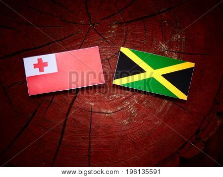 Tongan Flag With Jamaican Flag On A Tree Stump Isolated