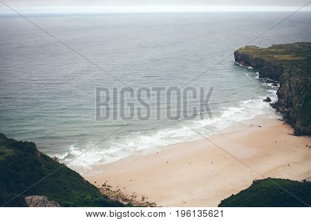 Wild beach on the ocean with less number of people. Mountain on background seascape dramatic atmosphere. Relax view waves water sea mock-up nature evening concept perspective
